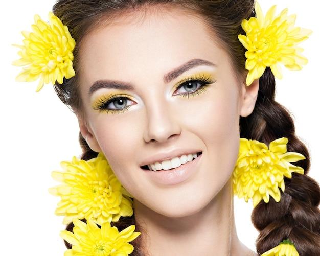 Zbliżenie twarzy młodej uśmiechniętej pięknej kobiety z jasnożółtym makijażem portret mody atrakcyjna dziewczyna z warkoczykami stylowe fryzury na białym tle profesjonalny makijaż