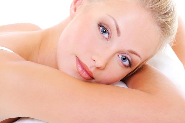 Zbliżenie twarzy pięknej blond kobiety o niebieskich oczach i zdrowej skórze