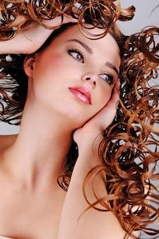 Zbliżenie twarzy pięknej dziewczyny z długimi włosami kręconymi - niski kąt