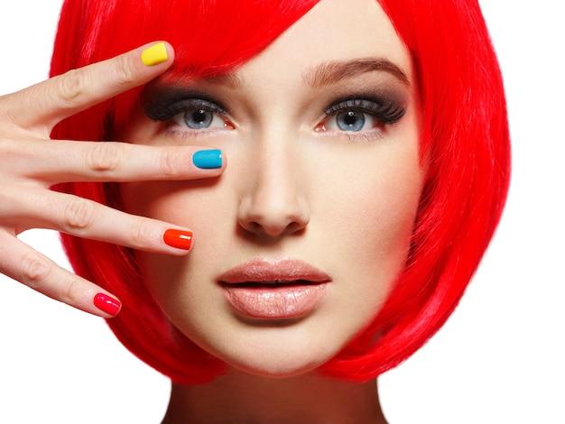Zbliżenie twarzy pięknej dziewczyny z jasnymi paznokciami multicolor
