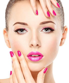 Zbliżenie twarzy pięknej dziewczyny z różowym makijażem oczu i jasnymi różowymi paznokciami. modelka pozowanie na białej ścianie