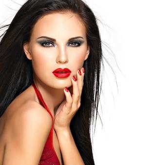 Zbliżenie twarzy pięknej kobiety brunetka z czerwonymi ustami i paznokciami