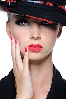 Zbliżenie twarzy pięknej kobiety z jaskrawoczerwonymi ustami i paznokciami w kapeluszu mody