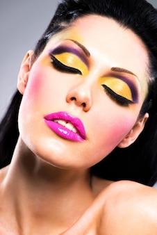 Zbliżenie twarzy pięknej kobiety z makijaż moda jasny kolor