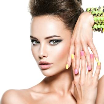Zbliżenie twarzy pięknej kobiety z wielobarwnymi paznokciami