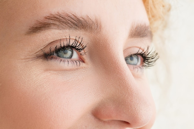 Zbliżenie twarzy pięknej młodej kobiety rasy kaukaskiej, skup się na oczach