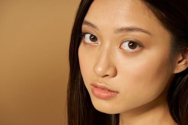 Zbliżenie twarzy pięknej młodej kobiety rasy mieszanej ze świecącą skórą patrzącą na kamerę
