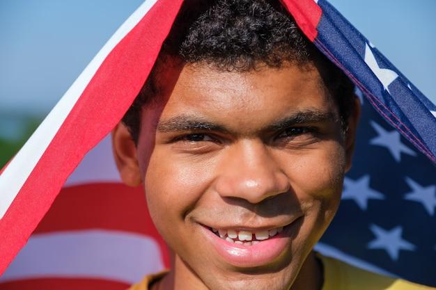 Zbliżenie twarzy szczęśliwego afro-amerykanina owija się w amerykańską flagę i patrzy w kamerę i uśmiecha się na zewnątrz latem