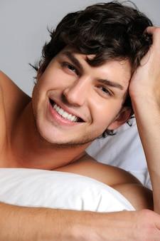 Zbliżenie twarzy uśmiechniętego szczęśliwego młodego człowieka leżącego w łóżku