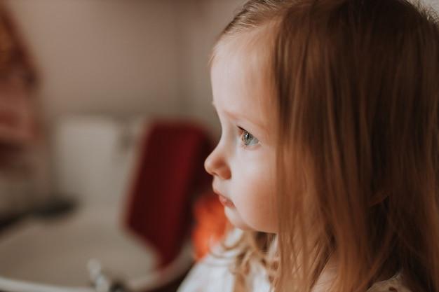 Zbliżenie twarzy w profilu ślicznej małej blondynki z zielonymi oczami, miejscem na tekst