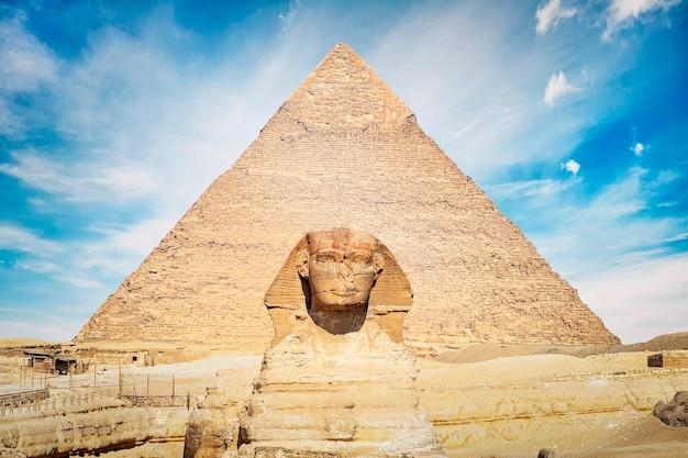 Zbliżenie twarzy wielkiego sfinksa z piramidą w tle w piękny pochmurny dzień błękitnego nieba w gizie, kair, egipt. przedni widok