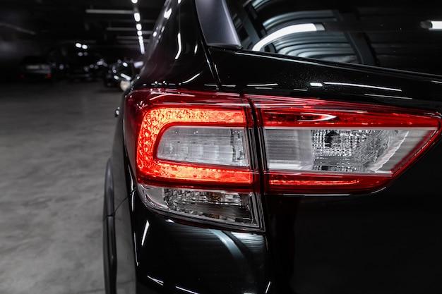 Zbliżenie tylnego światła nowego crossovera z czarnym halogenem. zewnętrzna część nowoczesnego samochodu