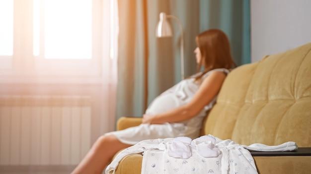 Zbliżenie ubrania noworodka na niewyraźne tło kobiety w ciąży, światło słoneczne