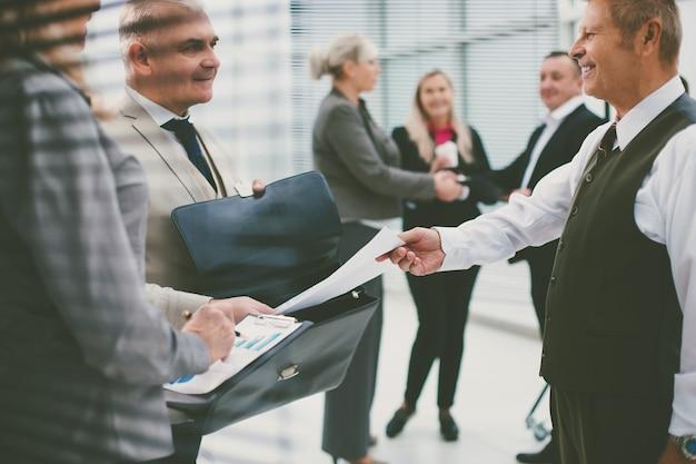 Zbliżenie udanego biznesmena, który przekazuje dokument swojemu partnerowi biznesowemu