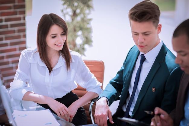 Zbliżenie udany zespół biznesowy siedzący przy biurku w życiu biurowym
