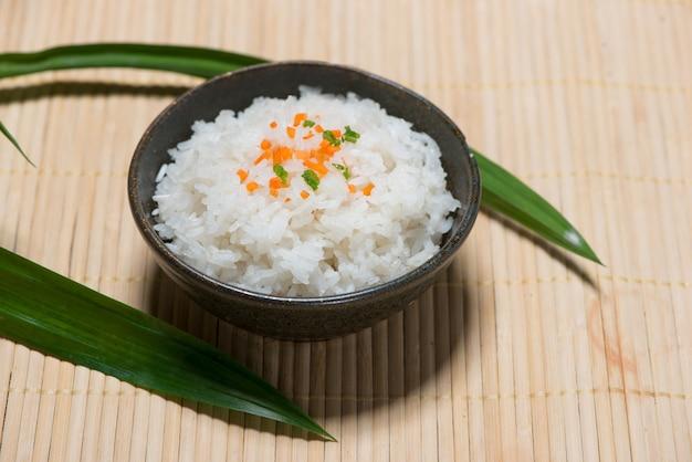 Zbliżenie ugotowanego ryżu w drewnianej misce na drewnianym stole