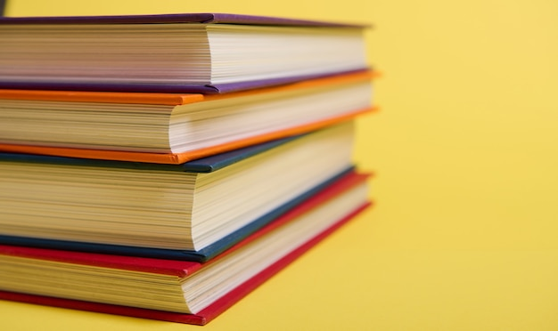 Zbliżenie ułożone wielobarwne książki na żółtym tle powierzchni z miejsca kopiowania tekstu. koncepcja dnia nauczyciela, wiedza, literatura, czytanie, erudycja