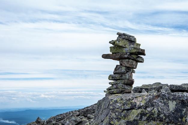 Zbliżenie ułożonych kamieni piramidy, które wyznaczają szlak górski, punkt orientacyjny dla pieszych wędrówek, symbol równowagi.