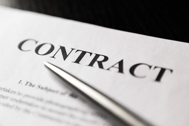 Zbliżenie umowy słowo ze srebrnym długopisem