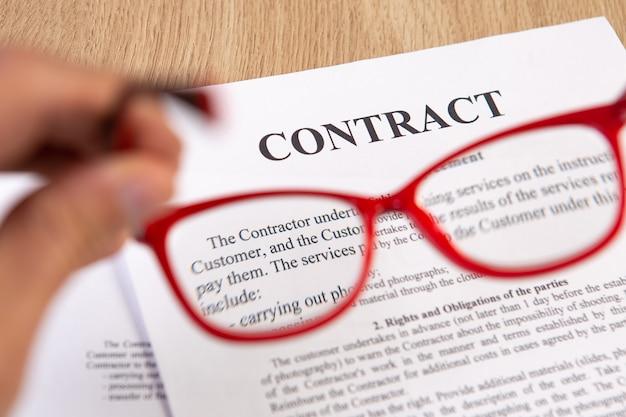 Zbliżenie umowy z czerwonymi okularami do czytania w ręku