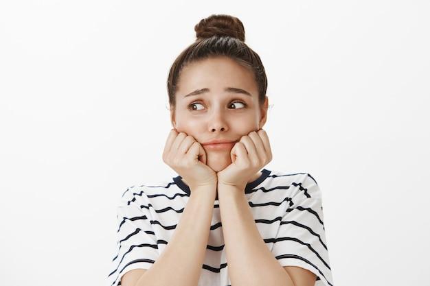 Zbliżenie: urocza i młoda dziewczyna opierając twarz na rękach i odwracając smutny, rozpaczliwy