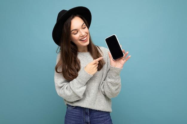 Zbliżenie urocza młoda kobieta szczęśliwa na sobie czarny kapelusz i szary sweter