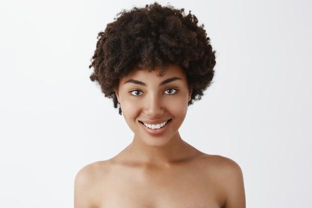Zbliżenie uroczego i naturalnego afroamerykanki z kręconymi włosami, stojącego nago i szeroko uśmiechającego się, kochającego i dbającego o własne ciało