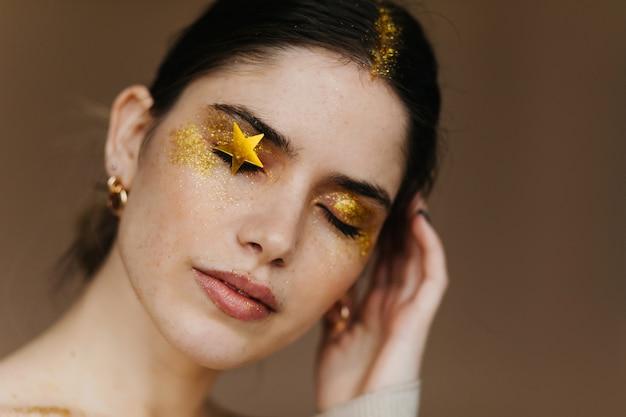 Zbliżenie uroczej czarnowłosej pani pozuje z zamkniętymi oczami. urocza dziewczyna z imprezowym makijażem.