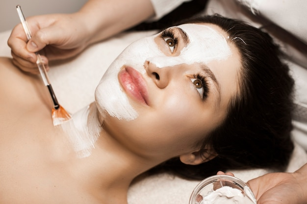 Zbliżenie uroczej kobiety o białej masce do pielęgnacji skóry na twarzy w uzdrowisku.