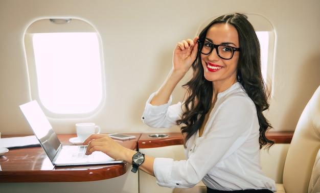 Zbliżenie uroczej kobiety w białej bluzce i okularach, która pisze coś na swoim laptopie, uśmiecha się i patrzy w kamerę, siedząc na fotelu przy oknie w samolocie.