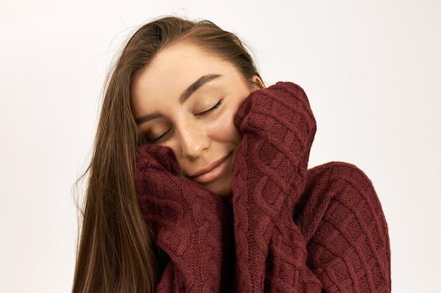 Zbliżenie uroczej młodej kobiety o ciemnych włosach czuje się przytulnie, ubrana w ciepły miękki sweter z długimi rękawami, z zamkniętymi oczami i radośnie się uśmiechającą
