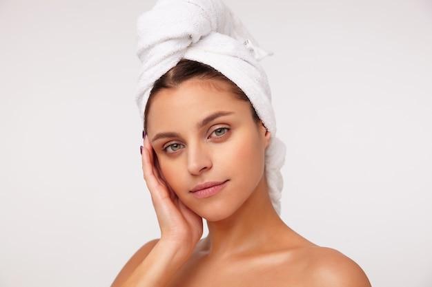 Zbliżenie uroczej młodej zielonookiej ciemnowłosej kobiety trzymającej podniesioną dłoń na jej policzku i delikatnie patrząc na aparat z lekkim uśmiechem, pozowanie po prysznicu na białym tle