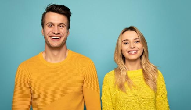 Zbliżenie uroczej pary, która pozuje w żółtych swetrach, patrząc w kamerę i uśmiechając się.