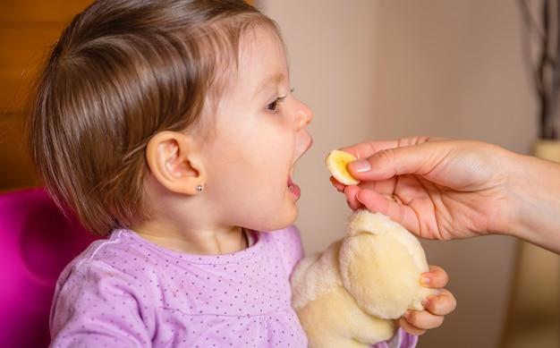 Zbliżenie uroczej szczęśliwej dziewczynki jedzącej plasterek banana z ręki matki w domu