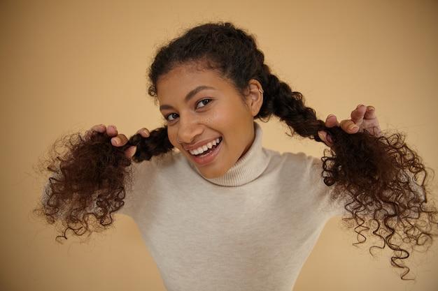 Zbliżenie uroczej wesołej młodej brunetki o ciemnej skórze, patrząc na kamery z szerokim, szczęśliwym uśmiechem i trzymającej splecione kręcone włosy, pozując na beżowym tle w codziennych ubraniach