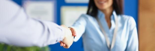 Zbliżenie uścisk dłoni bizneswoman z odznaką i klientem