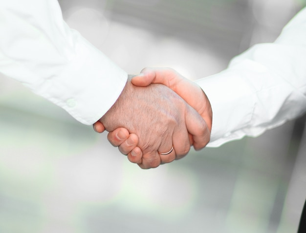 Zbliżenie. uścisk dłoni partnerów biznesowych na niewyraźne tło. pojęcie partnerstwa