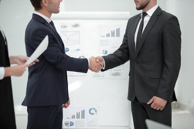 Zbliżenie. uścisk dłoni z partnerami biznesowymi przed prezentacją biznesową.
