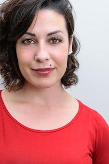 Zbliżenie uśmiechający się brazylijski kobieta ubrana w czerwoną koszulę i patrząc w kamerę.