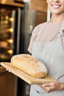 Zbliżenie uśmiechający się żeński pracownik piekarni w fartuchu trzyma biały bochenek chleba na drewnianej desce