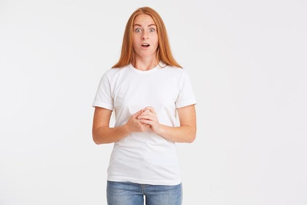 Zbliżenie uśmiechnięta atrakcyjna młoda kobieta z długimi rudymi włosami i piegami nosi koszulkę