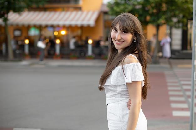 Zbliżenie: uśmiechnięta brunetka dziewczyna w białej sukni na tle ulicy i drogi. miejsce na twój projekt