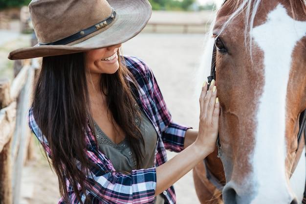 Zbliżenie uśmiechnięta delikatna młoda kobieta cowgirl w kapeluszu z koniem