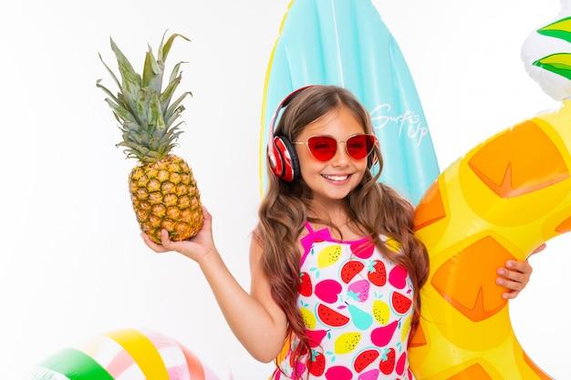 Zbliżenie uśmiechnięta dziewczyna na białej powierzchni, dziecko trzyma w rękach ananasa otoczonego pływackimi akcesoriami, czerwone słuchawki na głowie