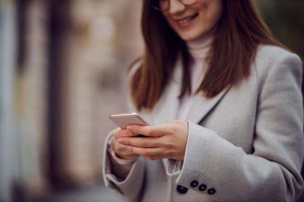 Zbliżenie uśmiechnięta dziewczyna w płaszczu stojąc na ulicy i za pomocą smartfona do sms-ów.