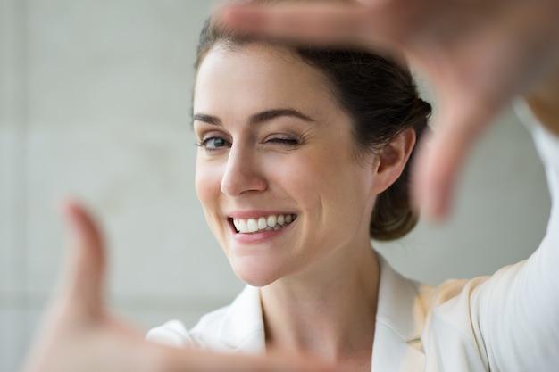 Zbliżenie uśmiechnięta kobieta podejmowania ramki gest