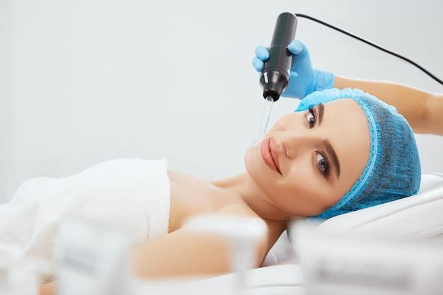 Zbliżenie uśmiechnięta kobieta w niebieskiej czapce, leżąc na kanapie w klinice kosmetologicznej i patrząc na kamery. ręce lekarza w niebieskich rękawiczkach wykonujących procedurę darsonwalizacji