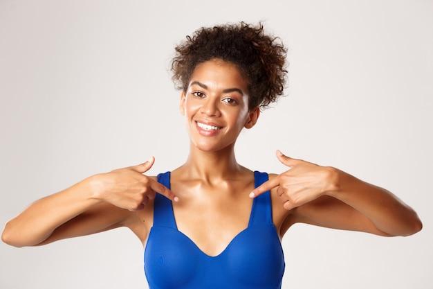 Zbliżenie: uśmiechnięta lekkoatletka afro-dziewczyna, wskazująca palcami na środku, pokazująca twoje logo