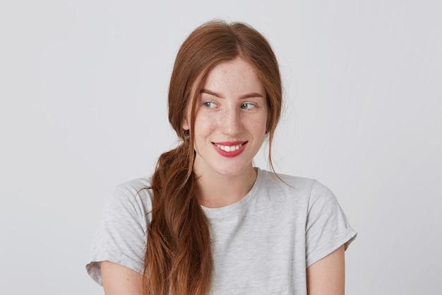 Zbliżenie uśmiechnięta młoda kobieta całkiem ruda z piegami nosi szarą koszulkę czuje się szczęśliwa i patrzy w bok