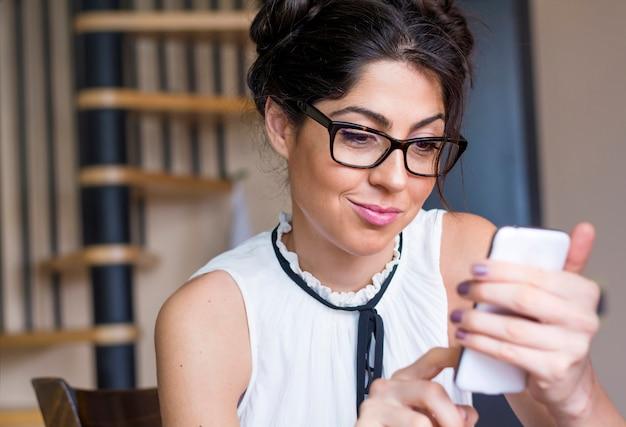 Zbliżenie uśmiechnięta nastolatka używając jej telefon